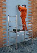 Prosty aluminiowy podest roboczy, idealny do robót wnętrzarskich.